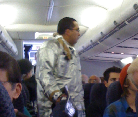 An airport fireman, wearing a hazmat suit, checks things out on our plane in El Paso