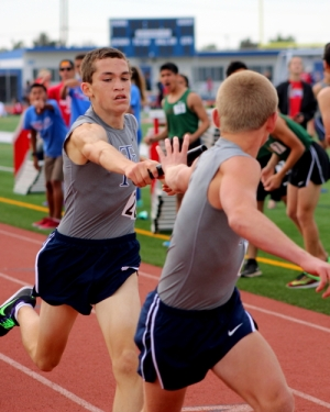 Jacob passes the baton to another runner in a relay race.